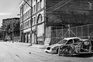 Black and white view of stripped car bodies on street next to shabby building.