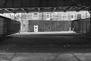 Black and white view of empty space under bridge, surrounded by steel fences and stone walls.