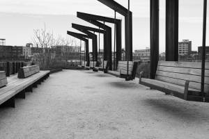 Black and white view of empty swing chairs and empty benches in Rail Line park.