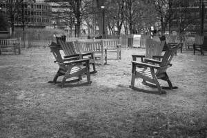 Black and white view of empty chairs and benches in park.