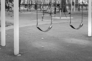 Black and white view of empty swings in playground.