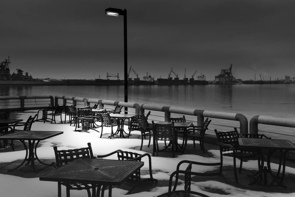 Black and white night view of empty tables outside a restaurant on the river with snow on the ground