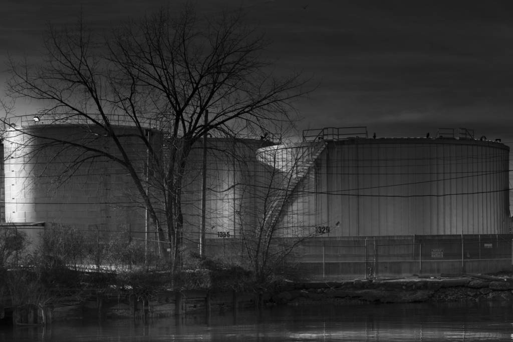 Black and white view of oil storage tank at night.